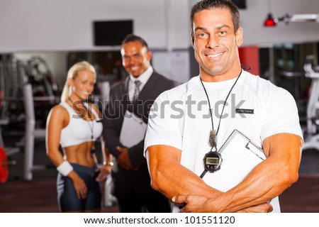 muscular senior gym trainer portrait with colleagues in background - stock photo