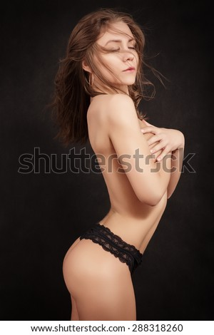 muscular sensual girl cover her beautiful bared breast on black background - stock photo