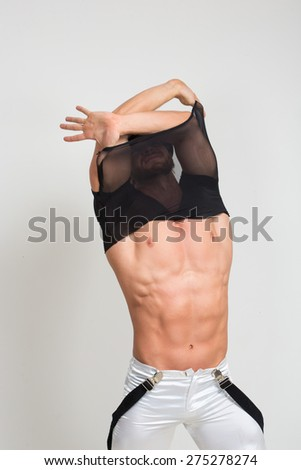 Muscular sexy man taking off t shirt. Sexy stripper undressing. - stock photo