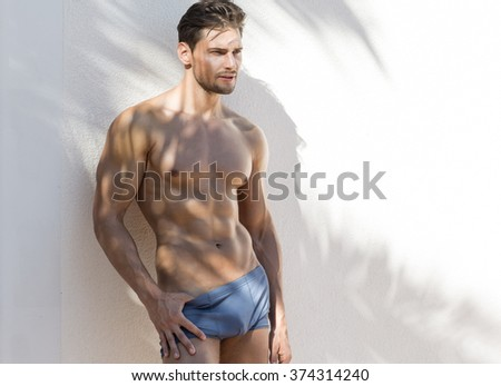 Muscular sexy model in beach shorts - stock photo