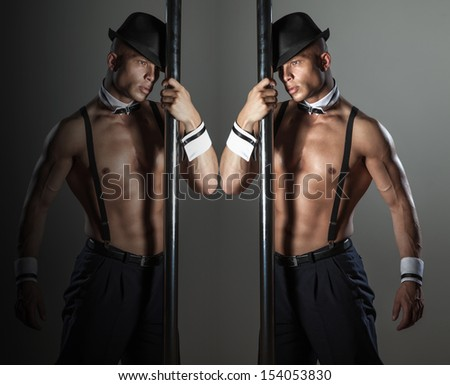 Muscular sexy naked man dancing in the studio in hat. - stock photo
