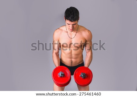 Muscular sexy shirtless young man exercising biceps with dumbbells, on grey background - stock photo