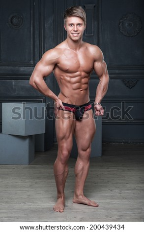 Muscular sexy young aesthetics naked smiling boy posing in underwear - stock photo