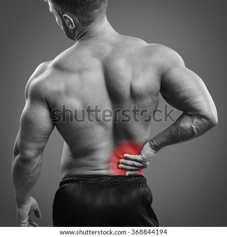 Muscular shirltess man with back pain over gray background. Concept with highlighted glowing red spot. - stock photo