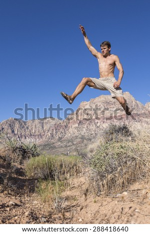 Muscular shirtless Caucasian man wearing shorts and sandals runs and jumps high in air over bushes in harsh desert landscape under clear sunny blue sky in Red Rock Canyon, Las Vegas - stock photo