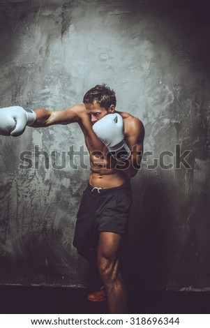 Muscular shirtless fighter showing his skills in studio over grey background. - stock photo