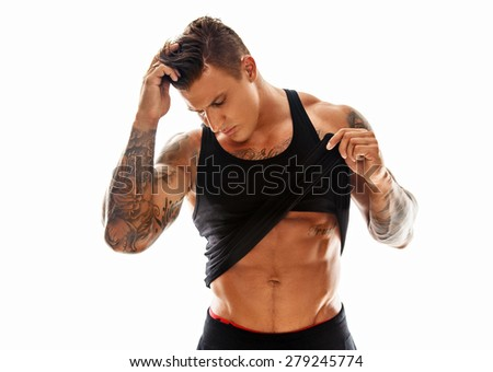 Muscular shirtless macho man in black undershirt posing in studio on white background - stock photo