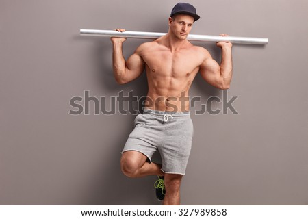 Muscular shirtless man carrying a gray metal pipe on his shoulders and leaning against a gray wall - stock photo