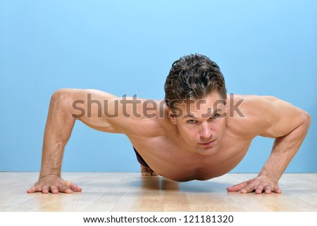 Muscular shirtless man performs modified pushup on wooden floor