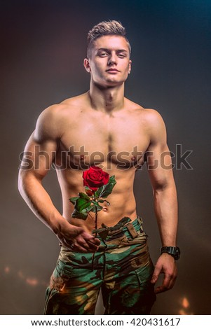 Muscular shirtless romantic macho man with rose - studio shot