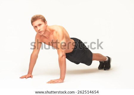 Muscular shirtless sportsman making push-ups on palms in studio with straight arms, looking at camera, isolated on white background, dressed in black shorts and black sneakers. Full length portrait - stock photo