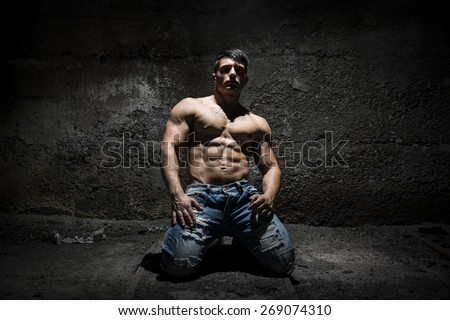 Muscular shirtless young man on his knees with light above head in grunge, vintage place - stock photo