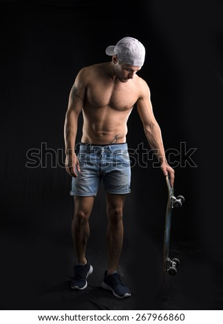 Muscular shirtless young man standing with skateboard in hand, looking down at it, on black background - stock photo