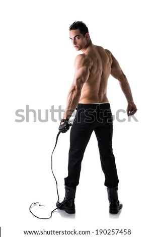 Muscular shirtless young man with whip and studded glove, full length shot from back - stock photo