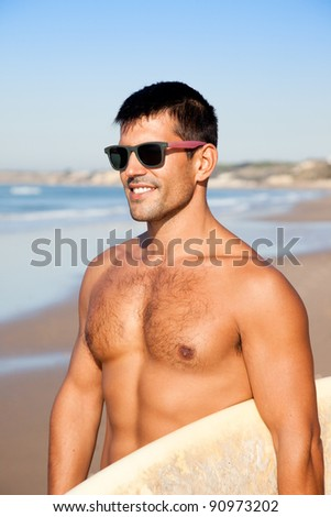 Muscular surfer wearing sunglasses smiling and holding his surf board overlooking the ocean. - stock photo