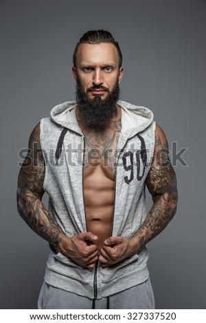 Muscular tattooed man with beard in grey zipuo hoodies. Isolated on grey background.