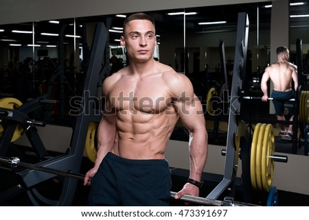 Muscular topless man sitting on the barbell in the gym
