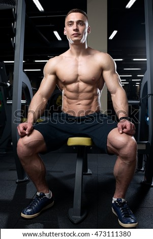 Muscular topless man sitting topless in the gym