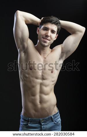 muscular torso of man on black bakground - stock photo