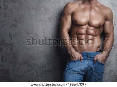 Muscular torso of man wearing jeans against concrete wall