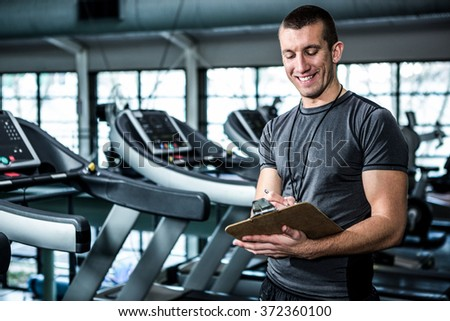 Muscular trainer writing on clipboard at the gym - stock photo