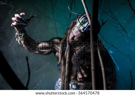 Muscular werewolf with dreadlocks with long nails among the branches of the tree. Gothic image of scary diabolical creatures for Halloween - stock photo