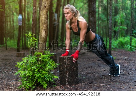 Muscular woman doing push-ups at park street work out. - stock photo