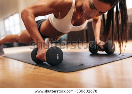 Muscular woman doing push-ups on dumbbells in gym. Powerful female exercising in health club. - stock photo