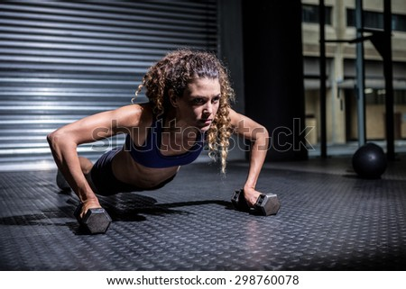 Muscular woman doing push-ups with dumbbells - stock photo