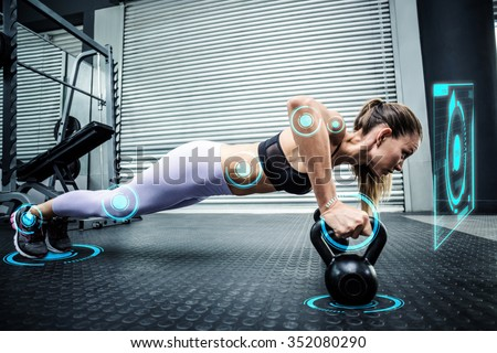 Muscular woman doing pushups with kettlebells against fitness interface - stock photo
