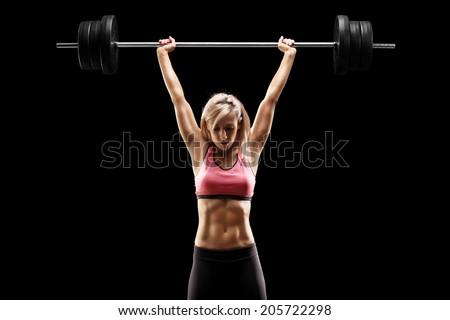 Muscular woman lifting a heavy barbell on black background - stock photo