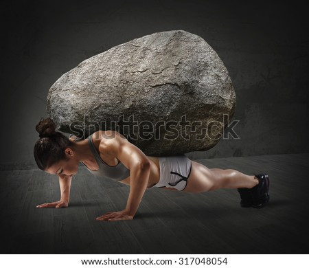 Muscular woman lifts a boulder with back - stock photo