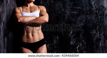 Muscular woman on a dark background