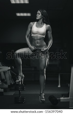Muscular woman posing in the gym with dumbbell. Black and white