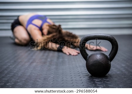 Muscular woman stretching in crossfit gym - stock photo