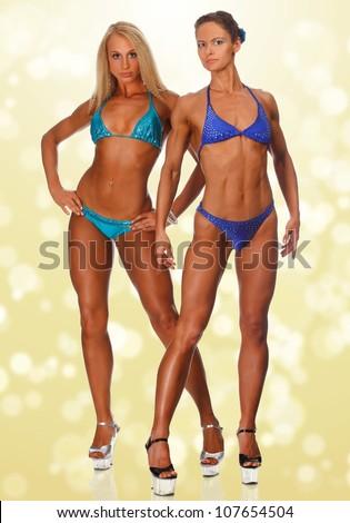 Muscular women on golden background - stock photo