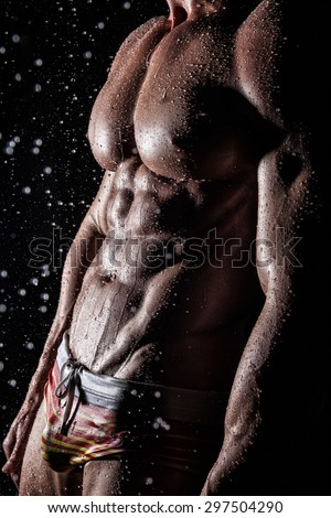 Muscular young athletic sexy man posing under the rain shirtless in underwear