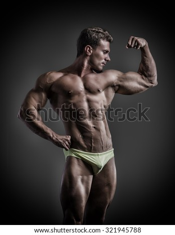 Muscular young bodybuilder in ckassic bicep pose, looking to a side. On dark background, wearing underwear