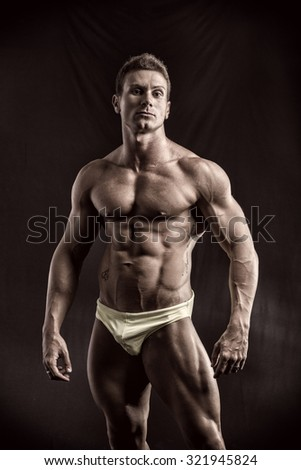 Muscular young bodybuilder in relaxed pose, looking at camera. On dark background, wearing shorts - stock photo