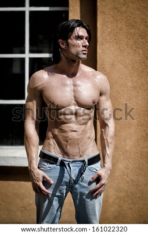 Muscular young bodybuilder shirtless outdoors in jeans - stock photo