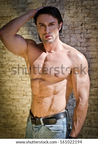 Muscular young bodybuilder shirtless outdoors in jeans, with hand on his head