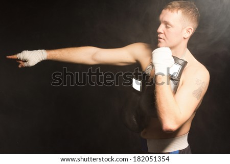 Muscular young boxer pointing with his bandaged hand extended in front of him as he stands with his other fist raised and his gloves dangling around his neck, side view on a dark background - stock photo