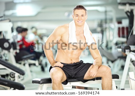 Muscular young guy sitting on a bench in a gym and looking camera, shallow depth of field - stock photo