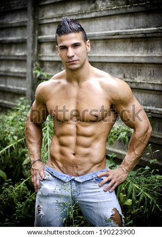 Muscular young latino man shirtless in jeans in front of concrete wall, with hands on hips - stock photo