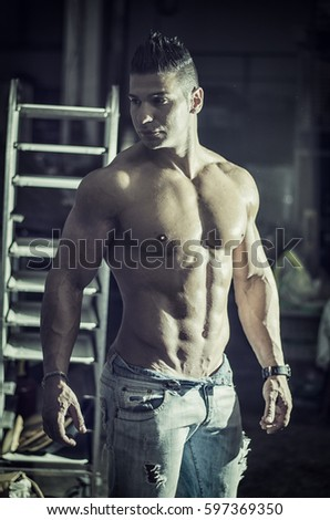 Muscular young latino man standing shirtless in jeans indoors, looking at camera