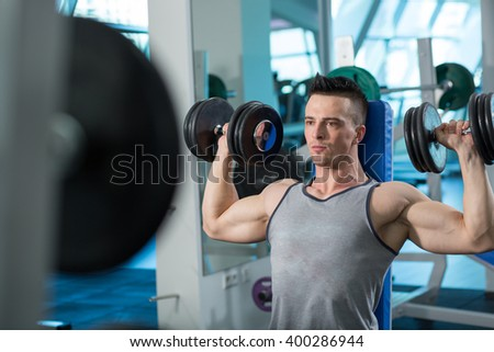 Muscular Young Man Doing Heavy Weight Exercise For Biceps With Dumbbells In Modern Fitness Center