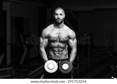 Muscular Young Man Doing Heavy Weight Exercise For Shoulders In Gym - stock photo