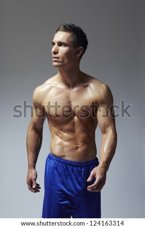 Muscular young man flexing arm muscles in sports outfit on white background