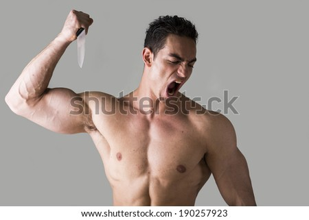 Muscular young man holding big knife ready to stab and screaming