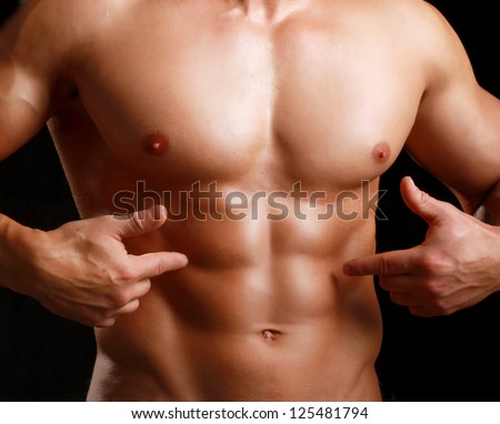 Muscular young man in black tank-top showing abs. - stock photo